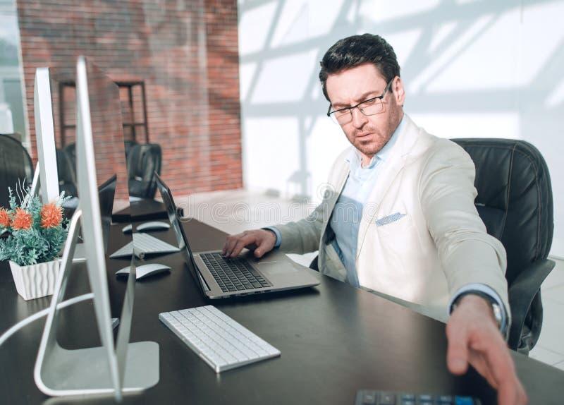 在玻璃之后 与坐在他的书桌的计算器的严肃的商人 免版税库存图片