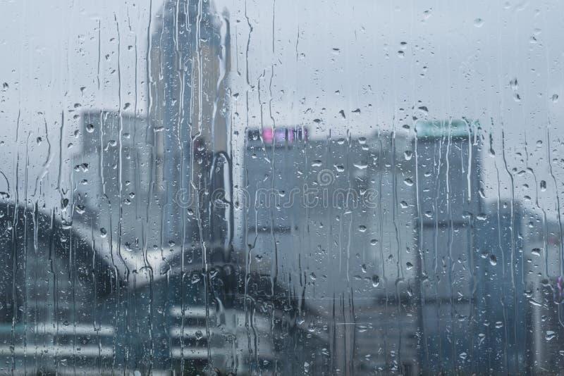 在玻璃后的香港在水滴的雨天在玻璃的 免版税库存照片