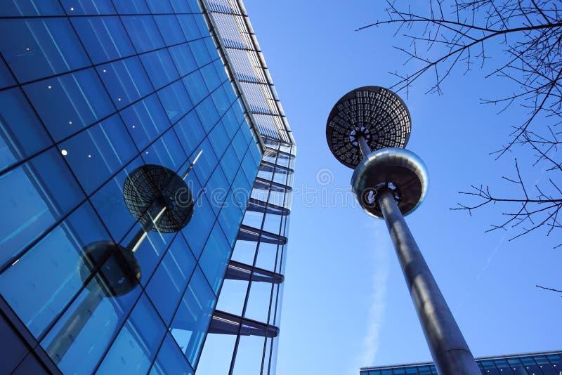 在玻璃和具体门面前面的灯岗位在一个现代公司skycraper大厦 图库摄影