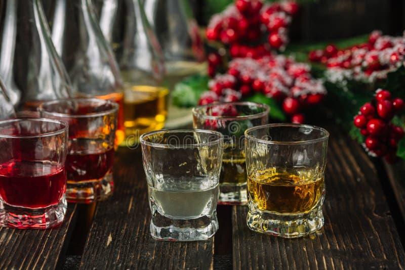 在玻璃和蒸馏瓶的被分类的酒精甘露酒有圣诞节装饰的 免版税图库摄影