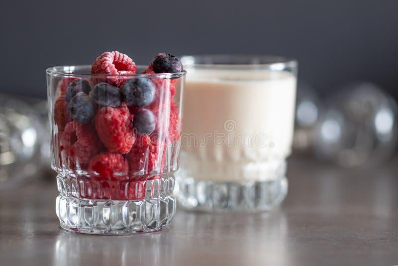 在玻璃和酸奶的冷冻莓 免版税库存图片