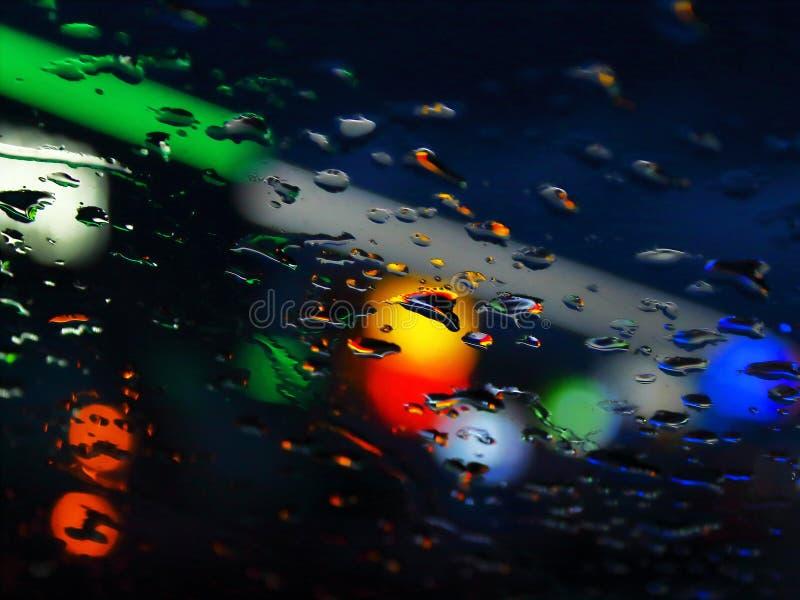 在玻璃夜城市的雨下落 库存照片