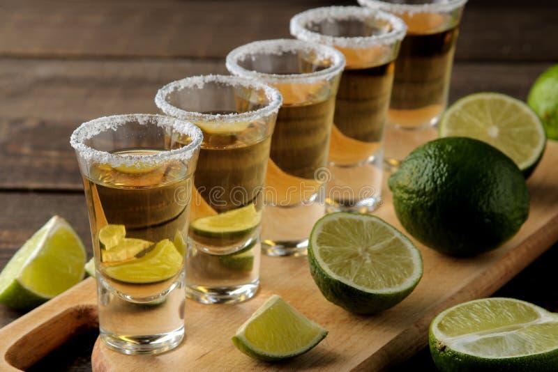 在玻璃小玻璃的金子龙舌兰酒与盐和石灰在棕色木背景 棒 酒精饮料 库存照片