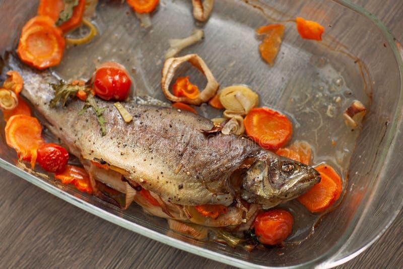 在玻璃平底深锅的煮熟的海鱼dorado用柠檬和香料和菜 烹调概念的自创食谱 免版税库存图片