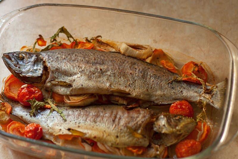 在玻璃平底深锅的煮熟的海鱼dorado用柠檬和香料和菜 烹调概念的自创食谱 图库摄影