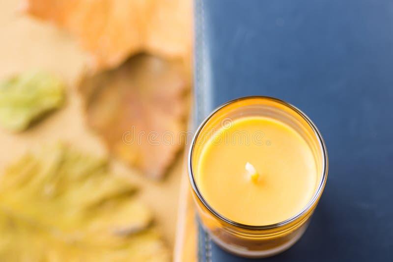 在玻璃持有人的橙色蜡烛在堆书深蓝海军背景 干燥黄色红色秋叶 舒适秋天大气 图库摄影