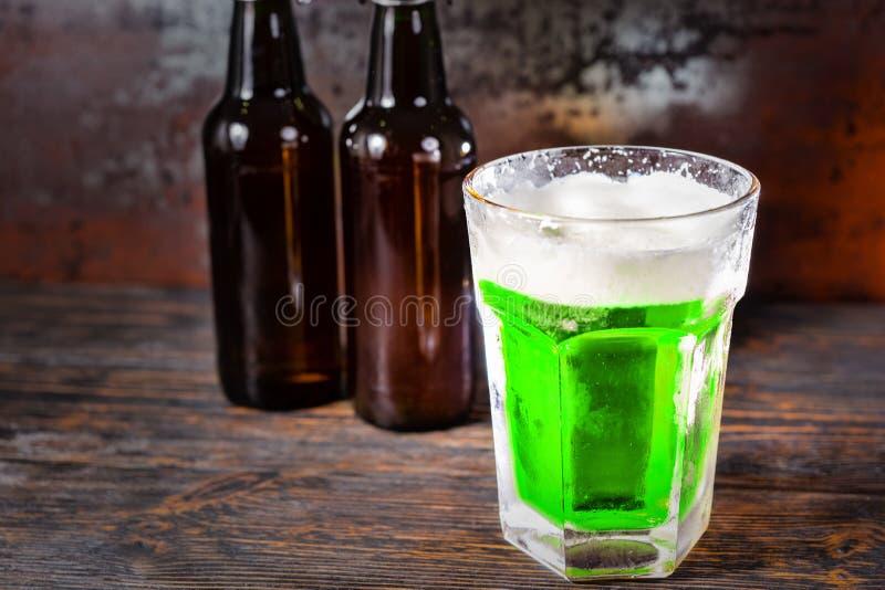 在玻璃旁边的两个啤酒瓶用绿色啤酒和f头.图片