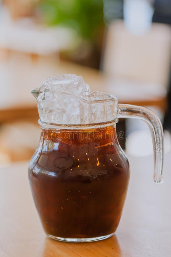 在玻璃杯子瓶子的被冰的咖啡拿铁黑褐色 免版税库存照片