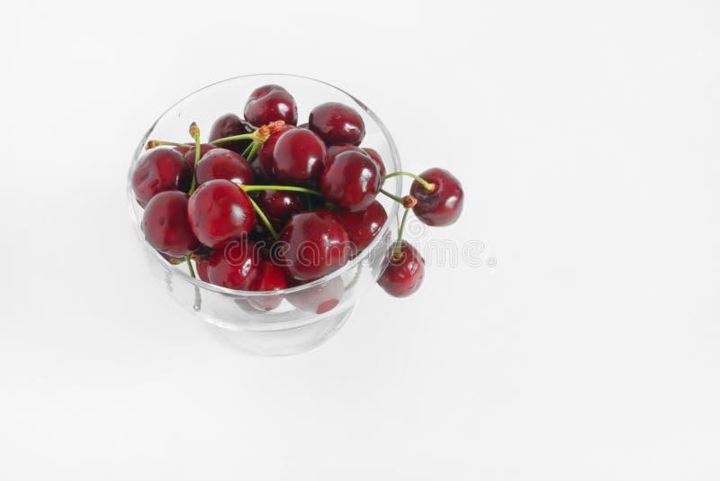 在玻璃杯子的成熟可口樱桃 在布料白色背景的新鲜的水多的莓果 鲜美季节性果子 库存图片