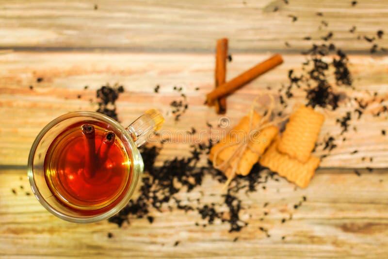 在玻璃杯子的热的茶用肉桂条茶叶和曲奇饼在木桌,平的位置上 免版税库存图片