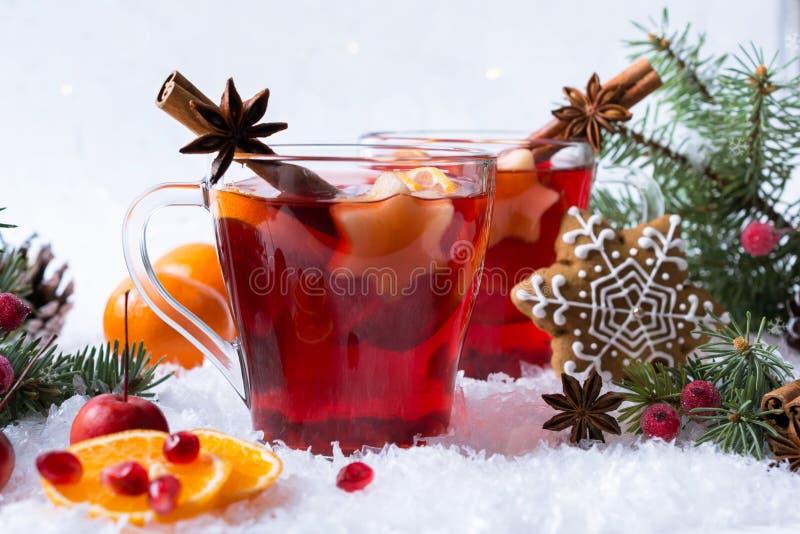 在玻璃杯子的热的被仔细考虑的加香料的红葡萄酒有有欢乐装饰光的和姜饼的 库存图片