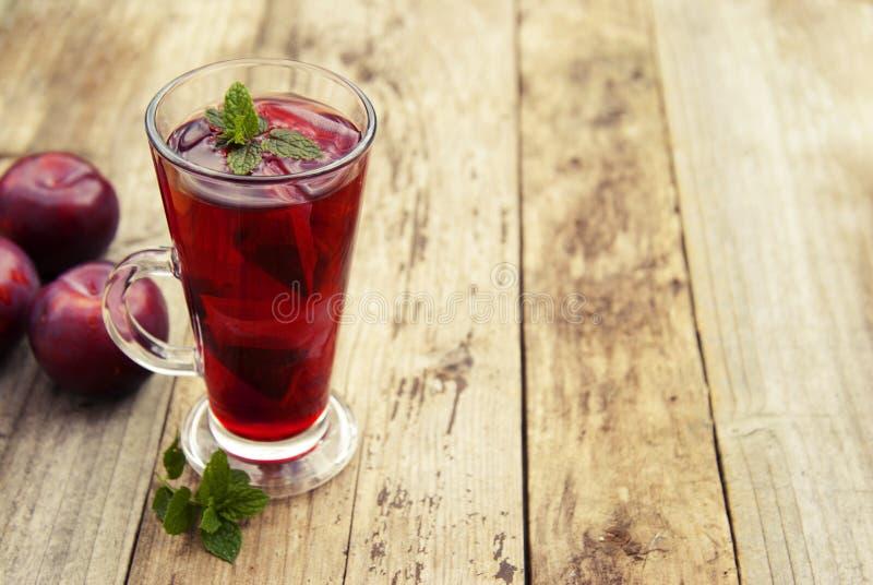 在玻璃杯子的红色草本和果子茶和茶用李子 土气织地不很细木桌 复制空间 免版税库存图片