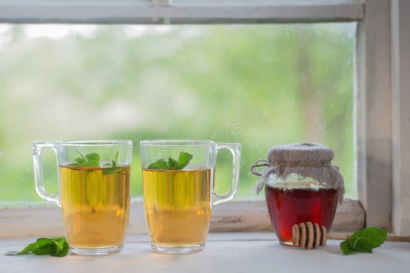 在玻璃杯子的茶在老窗台 库存图片