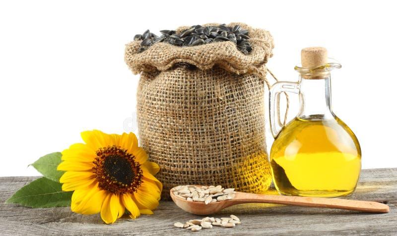 在玻璃水罐、种子和花的向日葵油在老木桌上有白色背景 免版税库存照片