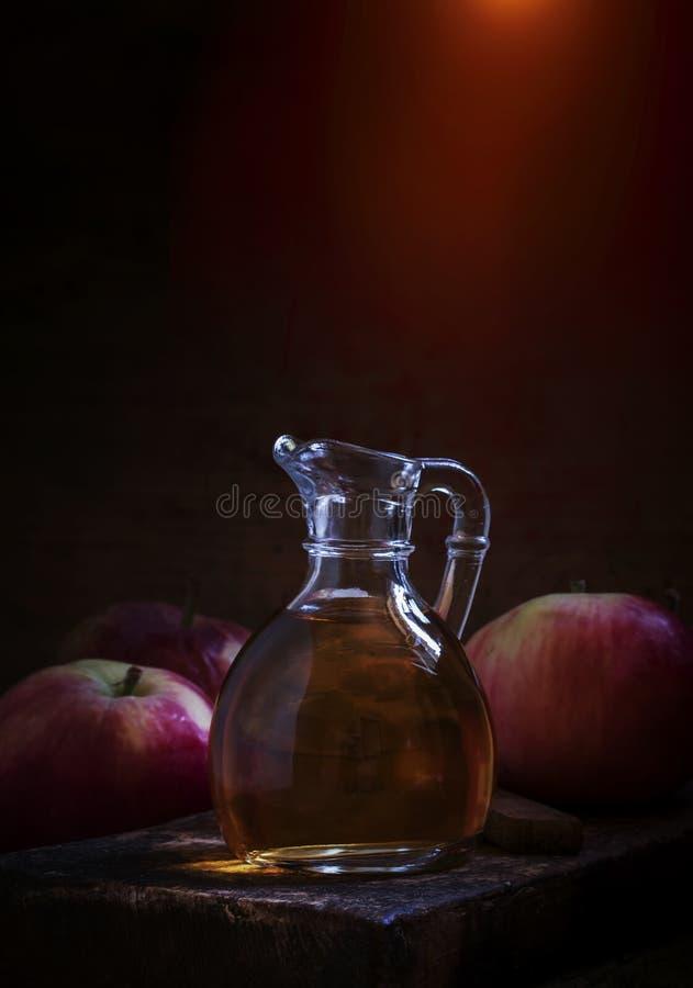 在玻璃水罐,新鲜的苹果,老木桌,低调,选择聚焦的苹果汁醋 免版税库存图片