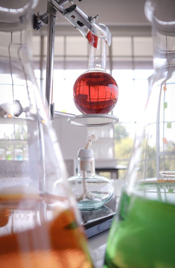 在玻璃测试的烧瓶的红色液体在机架 Alcolhol下灯地方与被弄脏的橙色和绿色化工实验室glasswa 免版税库存图片