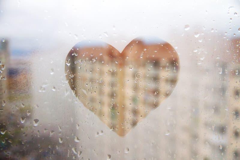 在玻璃湿窗口绘的心脏在城市 图库摄影
