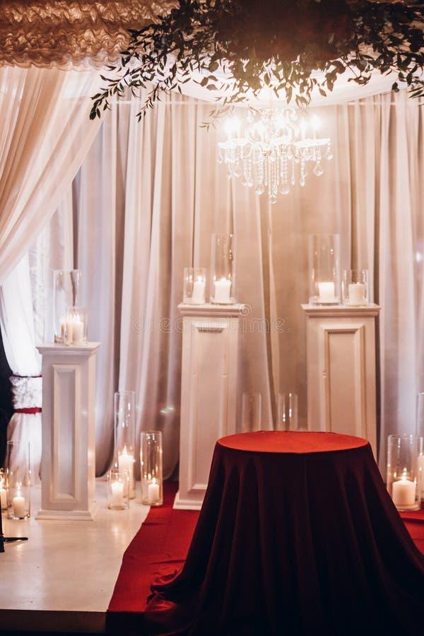 在玻璃灯笼的蜡烛和曲拱, ev的时髦的婚礼装饰 免版税库存照片