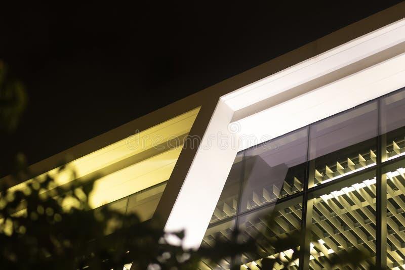 在玻璃现代办公楼里面射击的地面看法查寻在晚上 免版税库存照片