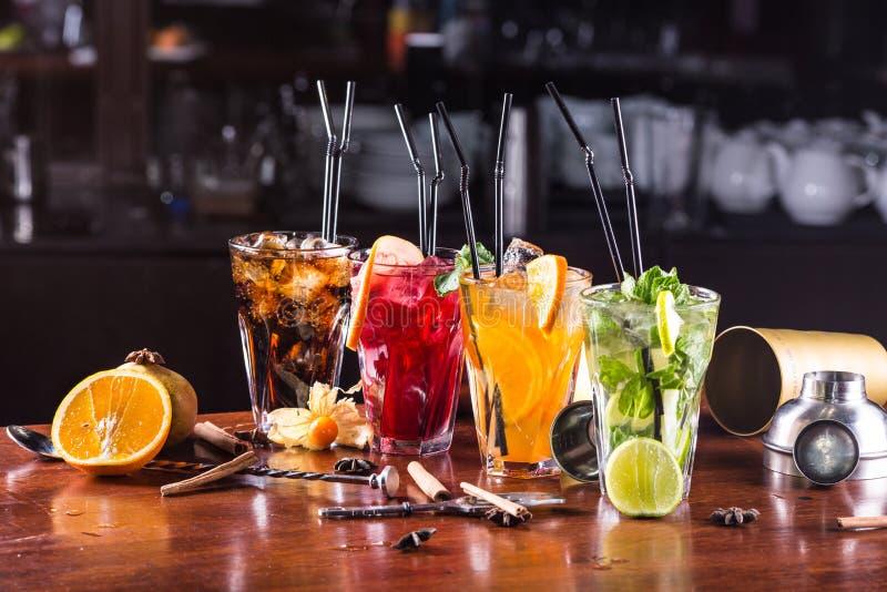 在玻璃玻璃的被分类的鸡尾酒在一个木立场 免版税库存图片