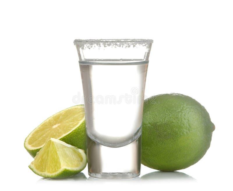 在玻璃玻璃的银色龙舌兰酒与石灰关闭在白色被隔绝的背景 图库摄影