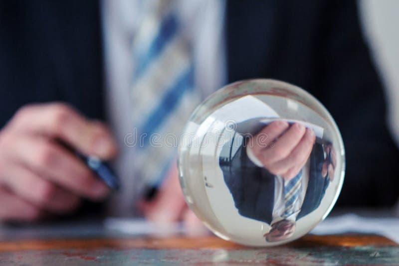 在玻璃球前面的商人签署的纸 库存照片