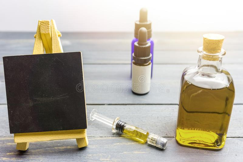 在玻璃瓶、大麻浆糊和黑板的Cbd油在桌上 库存照片