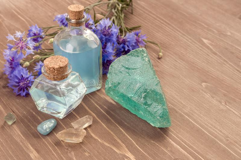 在玻璃瓶、自然石头和花的矢车菊花大海在棕色木背景 免版税库存照片
