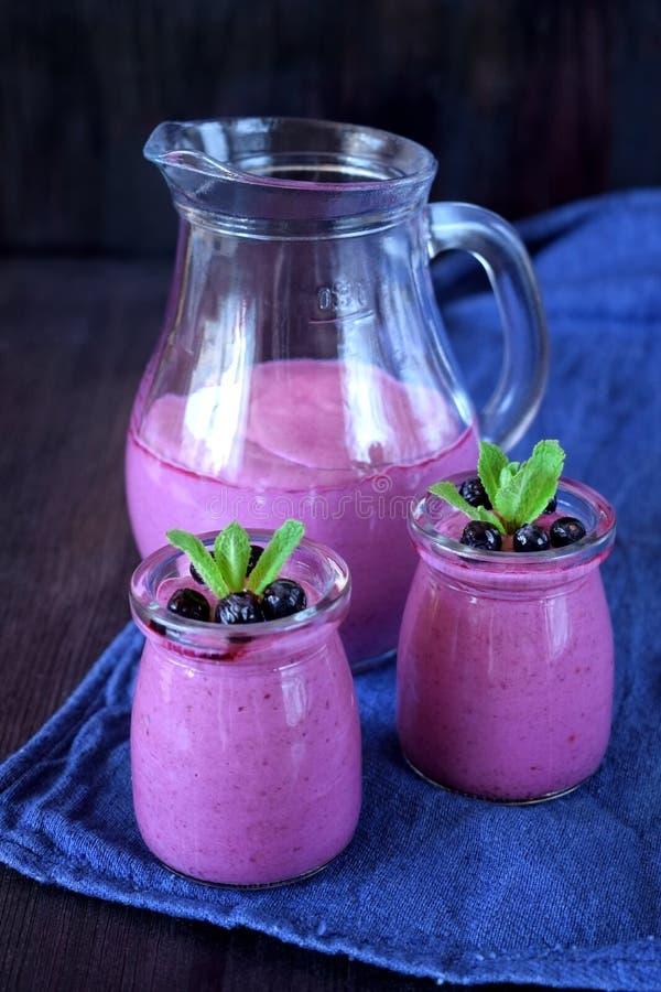 在玻璃瓶子和水罐的蓝莓圆滑的人 库存图片
