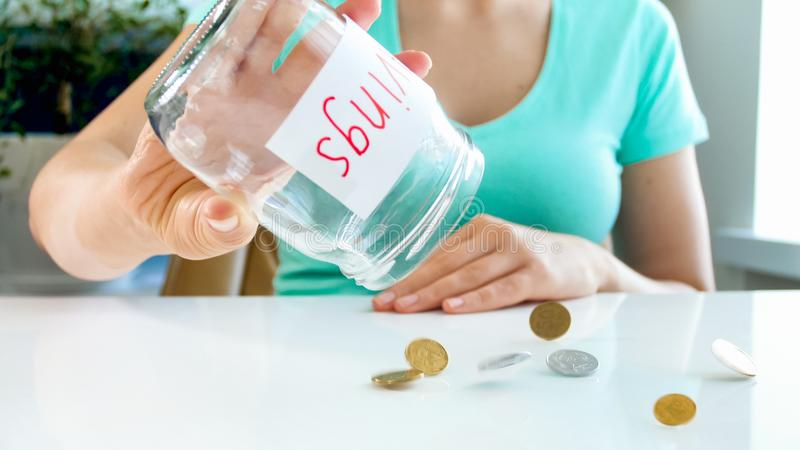 在玻璃瓶子外面的少妇倾吐的硬币特写镜头照片有金钱储款的 免版税库存图片