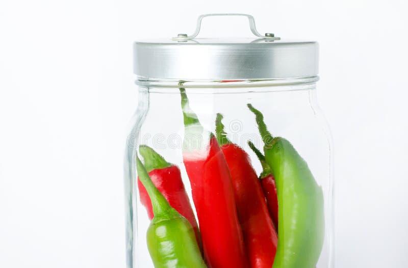 在玻璃瓶子的五颜六色的胡椒在白色背景 素食主义者食物概念 库存图片