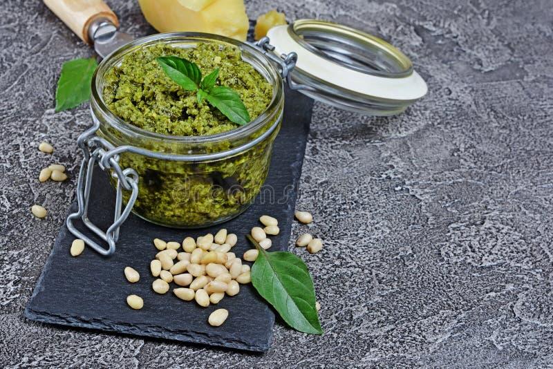 在玻璃瓶子的传统意大利绿色调味汁pesto用帕尔马干酪、松果和蓬蒿叶子在黑板岩板 库存照片