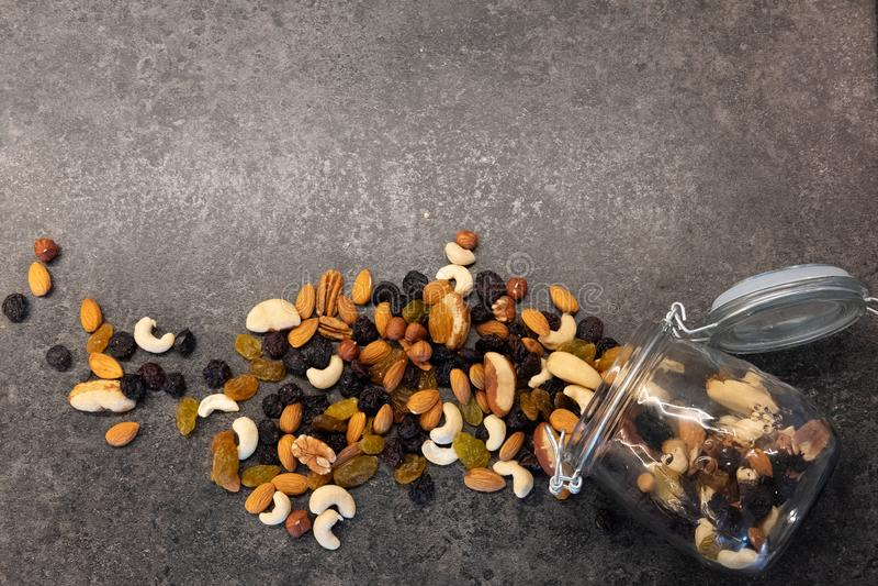 在玻璃瓶子的各种各样的坚果在黑暗的背景 健康食品和快餐 r 免版税库存照片
