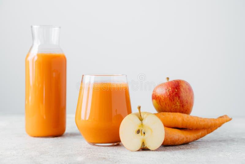 在玻璃瓶子的戒毒所饮料,在白色背景的切片苹果和红萝卜 清新自创自然红萝卜饮料,成熟果子 免版税库存照片