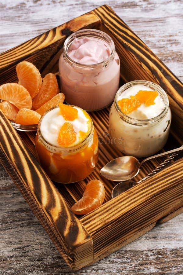 在玻璃瓶子的水果酸牛奶在一个木盘子 免版税图库摄影