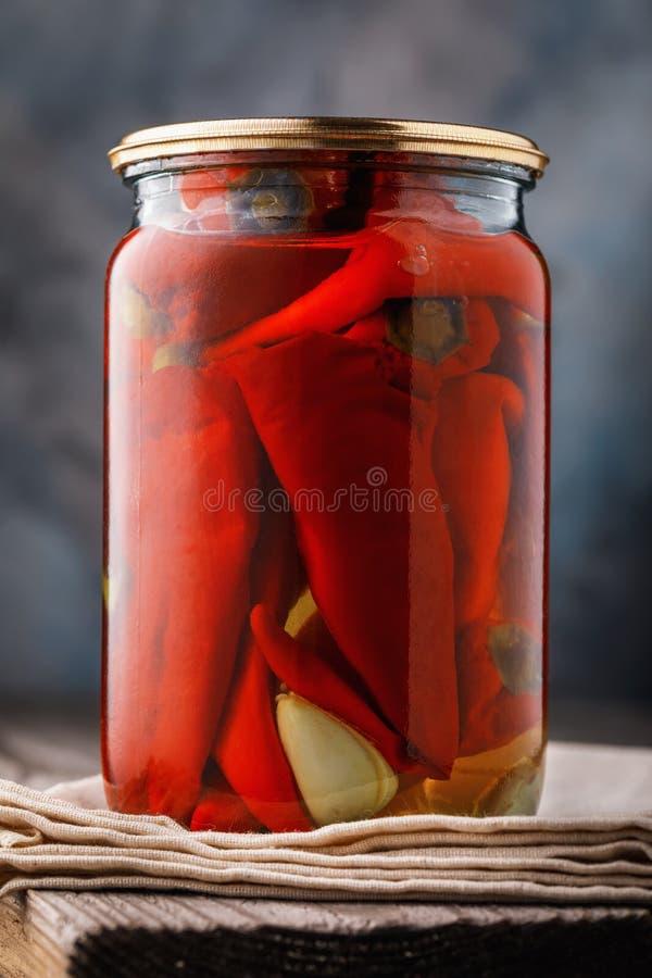 在玻璃瓶子的用卤汁泡的红辣椒在木桌上 免版税图库摄影