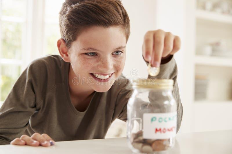 在玻璃瓶子的男孩保存的零用钱在家 免版税库存图片