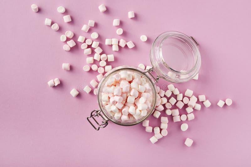 在玻璃瓶子的白色和桃红色蛋白软糖在桃红色背景 库存图片