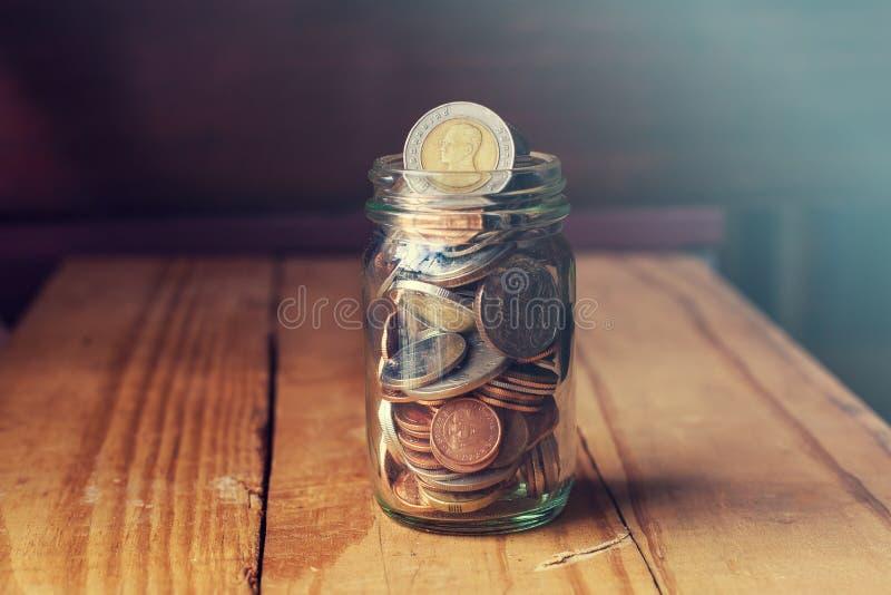 在玻璃瓶子的硬币在木桌,攒钱概念上 免版税库存照片