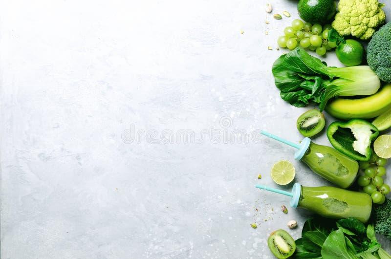 在玻璃瓶子的绿色圆滑的人有新鲜的有机绿色蔬菜和水果的在灰色背景 春天饮食,健康未加工 库存照片