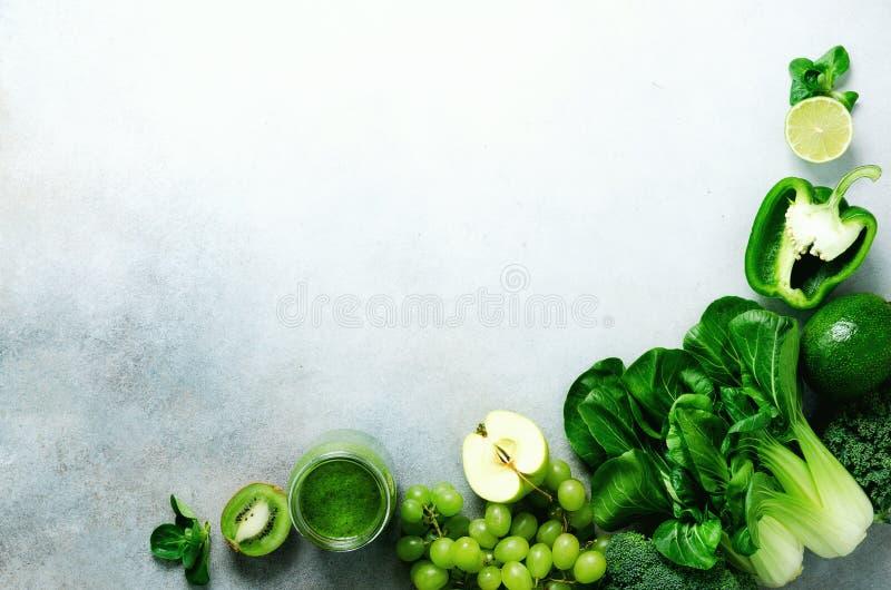 在玻璃瓶子的绿色圆滑的人有新鲜的有机绿色蔬菜和水果的在灰色背景 春天饮食,健康未加工 库存图片