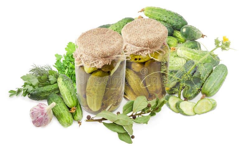 在玻璃瓶子的罐装黄瓜在新鲜的黄瓜和草本中 库存图片
