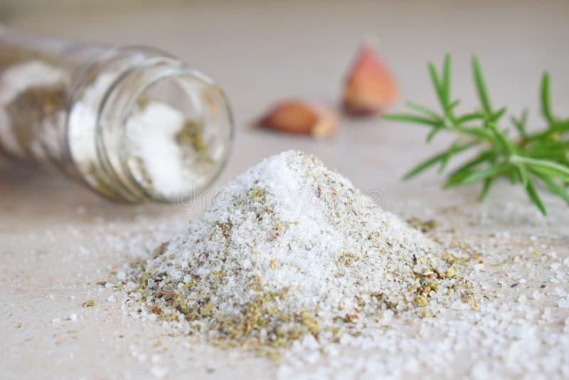 在玻璃瓶子的草本盐 海盐用芳香草本-迷迭香和大蒜 复制空间 免版税库存照片