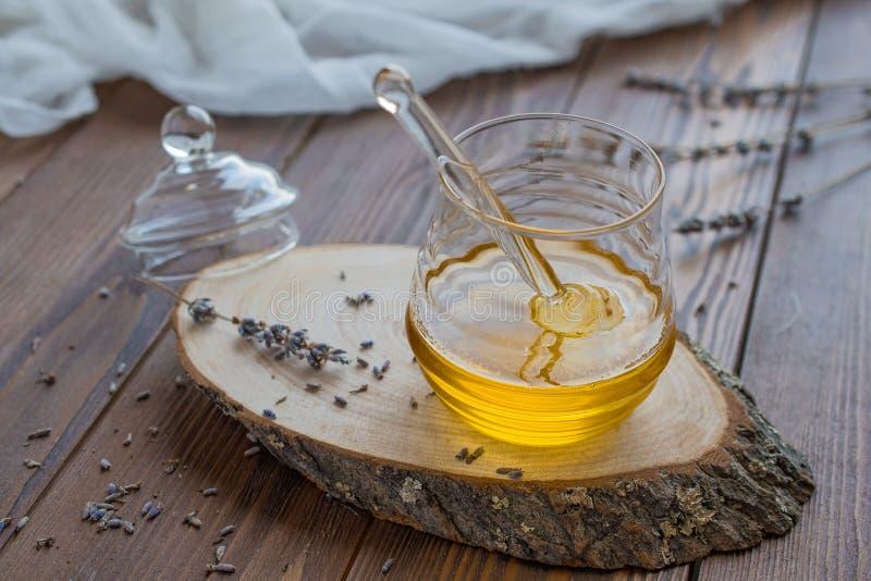在玻璃瓶子的蜂蜜有在土气木背景的蜂蜜浸染工的 免版税库存图片