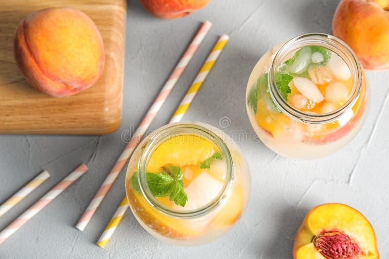在玻璃瓶子的鲜美桃子鸡尾酒在桌上 免版税图库摄影