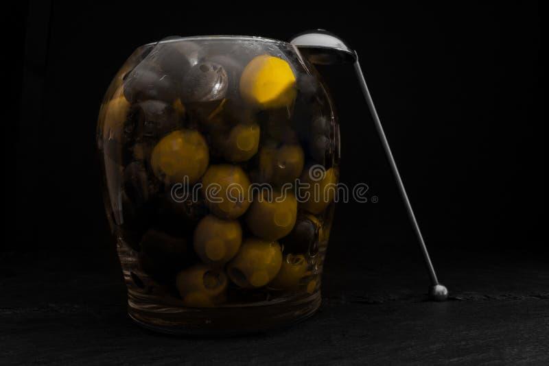 在玻璃瓶子的黑和绿橄榄有金属匙子的 库存图片