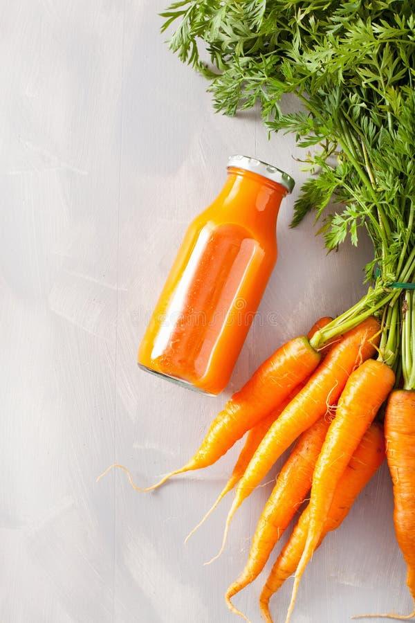 在玻璃瓶子,橙色红萝卜的水果和蔬菜圆滑的人 库存图片