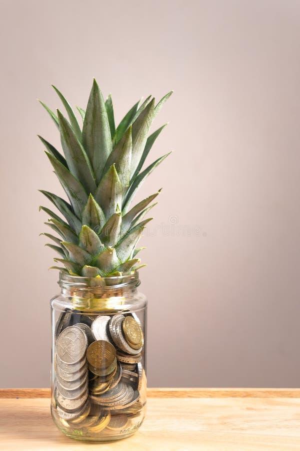 在玻璃瓶的便士有在上部的菠萝叶子的 免版税图库摄影
