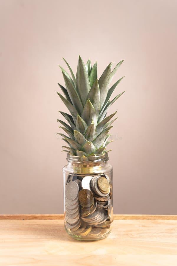 在玻璃瓶的便士有在上部的菠萝叶子的 库存图片