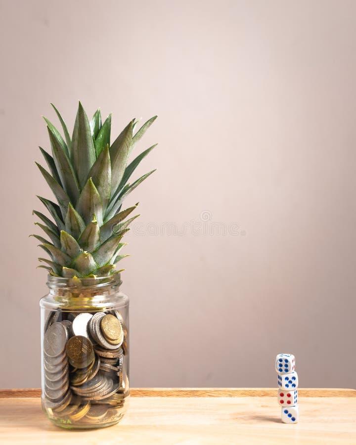在玻璃瓶的便士用菠萝在上部在另一边生叶并且切成小方块 库存照片